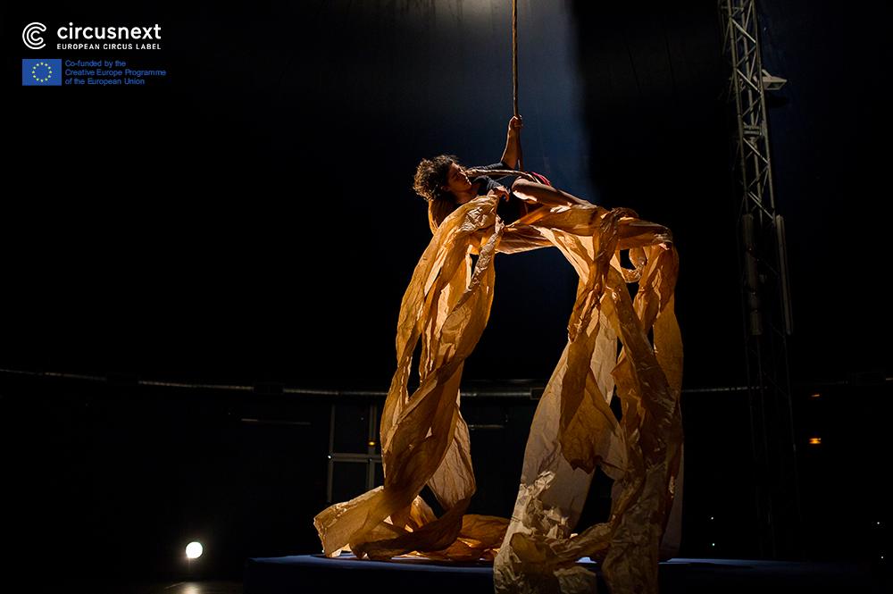 Sirkustaiteilija roikkuu köydessä tummasävyisellä esiintymislavalla, ja hänestä roikkuu suuria, vaaleita muovikaistaleita.