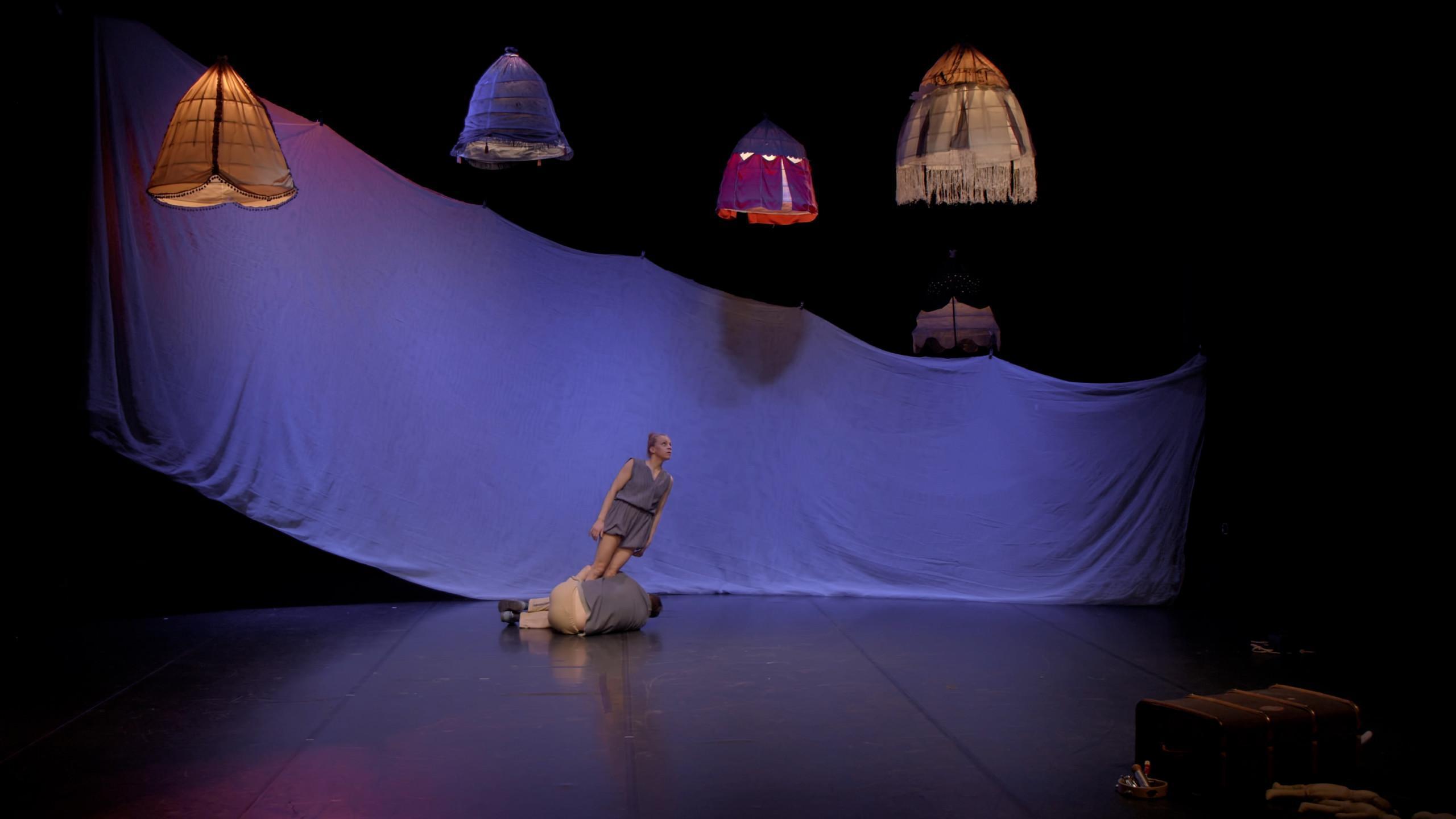 Esiintymislavalla on taustalla valkoinen kangas sinisissä valoissa, katosta roikkuu kankaisia lampunvarjostimia. Lavalla mies on sikiöasennossa ja pitää kiinni oikealle nojaavan naisen jaloista.