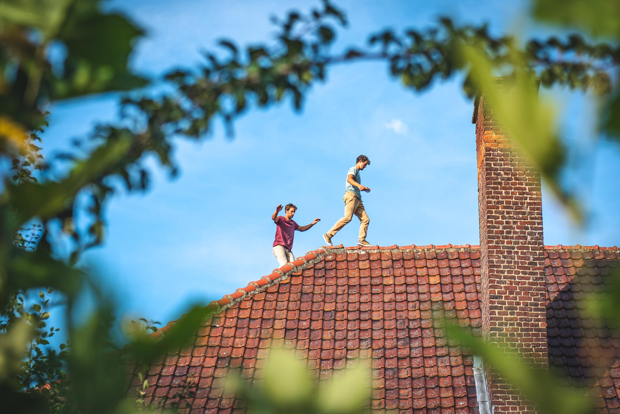 Two men walking on a rooftop made of red tiles.